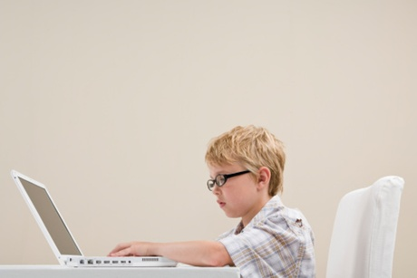Boy (10-11) using laptop, side view